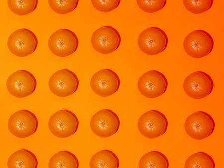 Colorful fruit pattern of fresh mandarins on an orange background. Top view