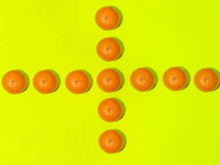 Colorful fruit pattern of fresh mandarins on a light green background. Top view