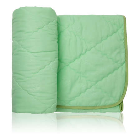 Folded soft green blanket, blanket or coverlet, on a white background with reflection