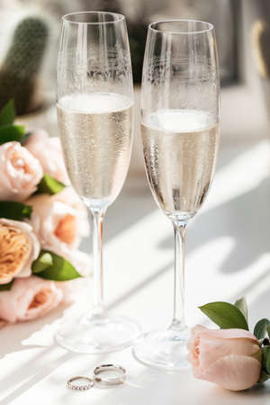 Wedding rings lie next to two glasses of champagne and a bouquet of roses in the sun