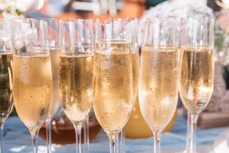Glasses of chilled champagne stand on a table with a tablecloth for a welcome treat for guests of the event