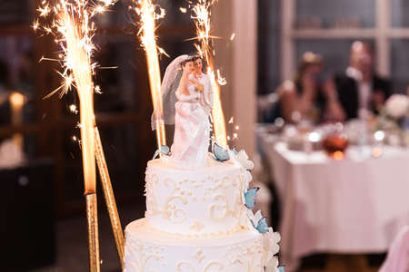White wedding cake with smokeless holiday candles and butterflies