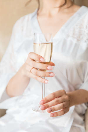 bride's hand with beautiful manicure and engagement ring and champagne Stockfoto
