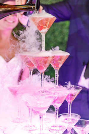 Slide of champagne with dry ice and smoke at the solemn event. Pyramid of glasses with alcohol and cherries.
