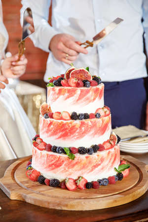 Wedding cake with many different fruits and wild berries and figs on top