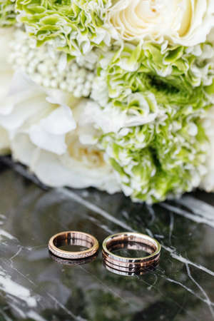 Wedding rings and a bouquet lie on a dark marble table