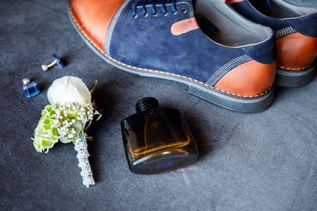 Blue cufflinks, boutonniere, toilet water and groom's shoes