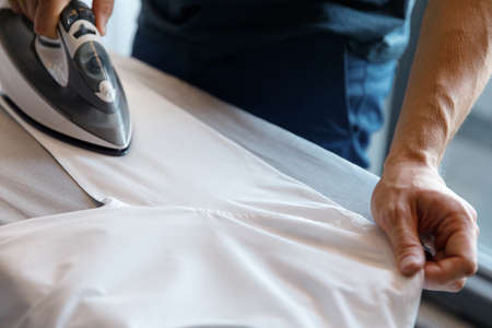 Man ironing white shirt, men's hands and iron, side view, cropped image, close up Stockfoto