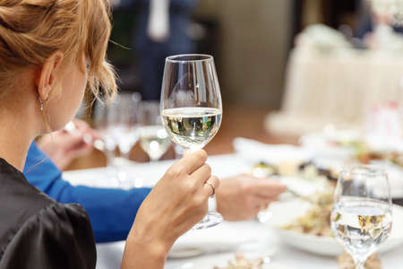 Glass of champagne in the hands of a girl at the festive table Stockfoto