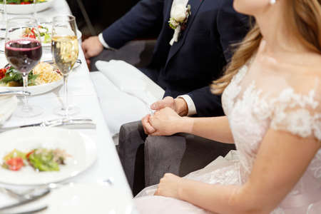 newlyweds hold hands in a restaurant during a wedding celebration