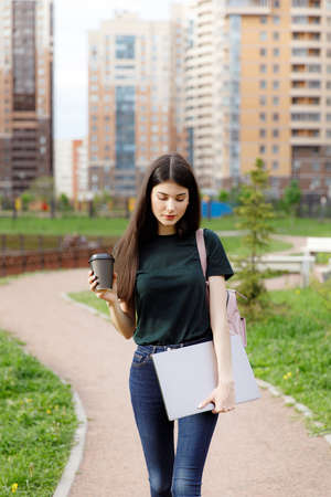 Beautiful young brunette woman carrying backpack and drinking takeaway coffee while walking outdoors Stockfoto - 148951491