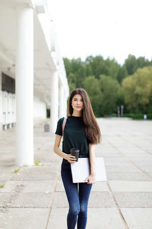 Beautiful young brunette woman carrying backpack and drinking takeaway coffee while walking outdoors Stockfoto - 148951616