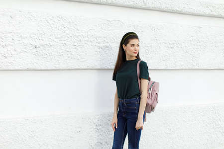 Brunette girl in jeans, a green T-shirt, a hair band and a pink backpack stands against a white wall Banque d'images