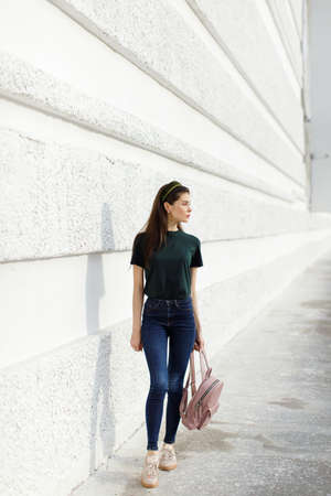 Brunette girl in jeans, a green T-shirt, a hair band and a pink backpack stands against a white wall Stockfoto - 148951634