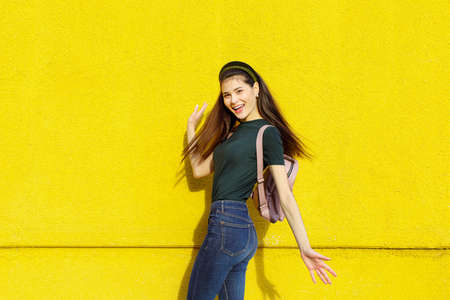 Young beautiful brunette girl in jeans, a green T-shirt, hair bands and a pink backpack posing on a yellow concrete wall Stockfoto - 148951708