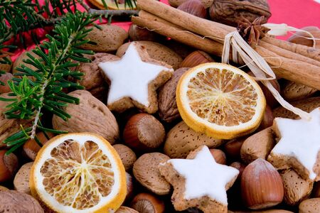 green sprig and star-shaped cinnamon biscuits with hazelnuts, almonds and oranges Stock Photo