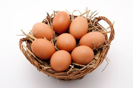 brown organic eggs in a basket with straw photo