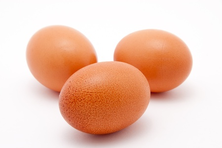three brown organic eggs on white background photo