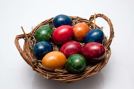 colorful easter eggs on straw in a basket on white background photo