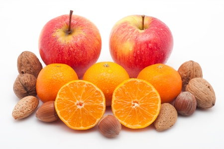 red apples, mandarins  with waterdrops and nuts on white background photo