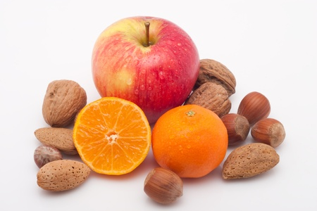 red apple, mandarins  with waterdrops and nuts on white background