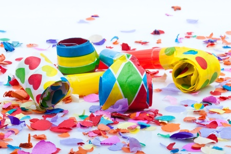 colorfull noisemakers for a party isolated on white background with confetti