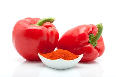 closeup of red, green, yellow and orange peppers and paprika in a dish isolated on white background Stock Photo