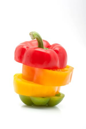 fresh slices of red, green, yellow and orange pepper isolated on white background photo
