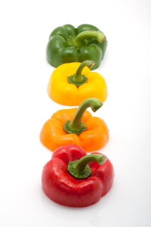 fresh slices of red, green, yellow and orange pepper with water drops isolated on white background photo