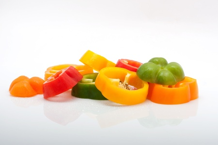 fresh slices of red, green, yellow and orange pepper with water drops isolated on white background