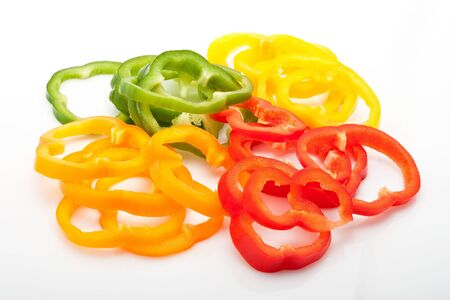 fresh slices of red, green, yellow and orange pepper isolated on white background