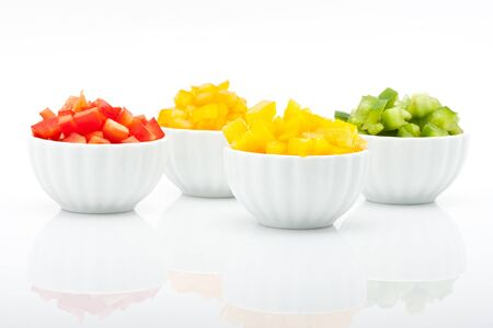 closeup of fresh green, yellow, orange and red peppers in bowl isolated on white background photo