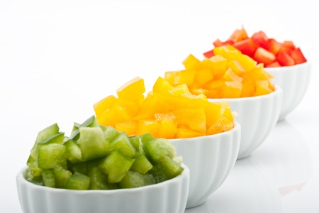 closeup of fresh green, yellow, orange and red peppers in bowl isolated on white background
