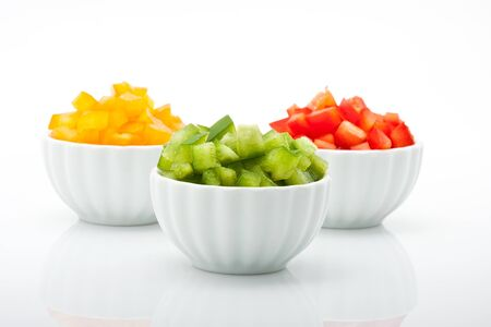 closeup of fresh green, yellow and red peppers in bowl isolated on white background  photo
