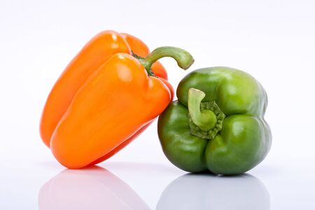 a pair of orange and green pepper isolated on white background Stock Photo