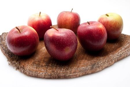 juicy sweet red apples on a raw board isolated on white background