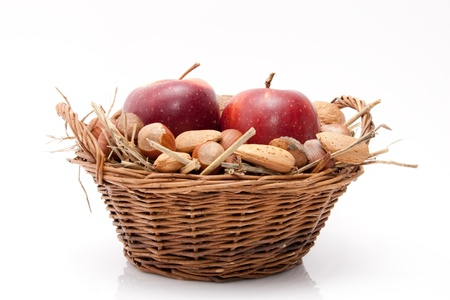 red apples and nuts in a basket isolated on white background Stock Photo