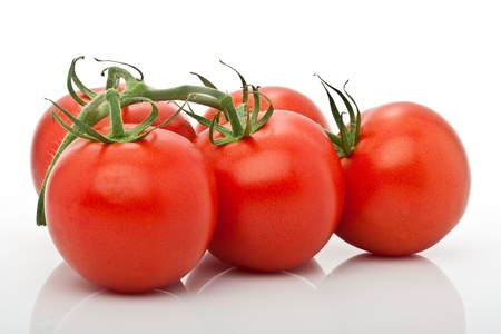 closeup of panicle of juicy tomatoes isolated against white background