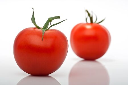 closeup of two juicy tomatoes isolated against white background