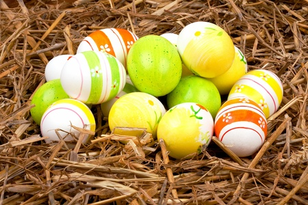closeup of colorful painted easter eggs hidden in a nest of straw