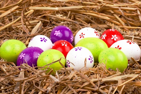 closeup of colorful painted easter eggs hidden in a nest of straw photo