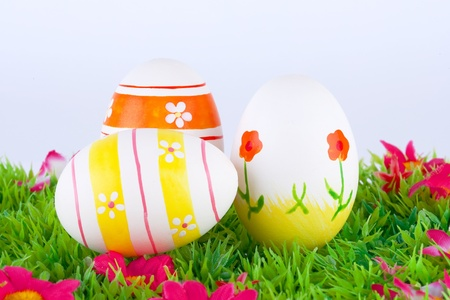 colorful painted easter eggs located on a green meadow with flowers