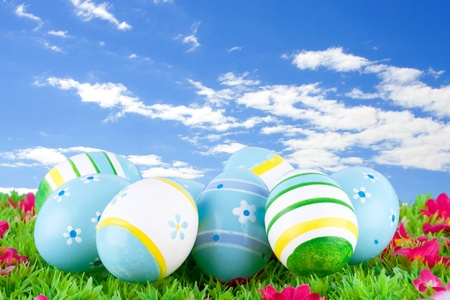 colorful painted easter eggs located on a green meadow with flowers in front of a blue sky