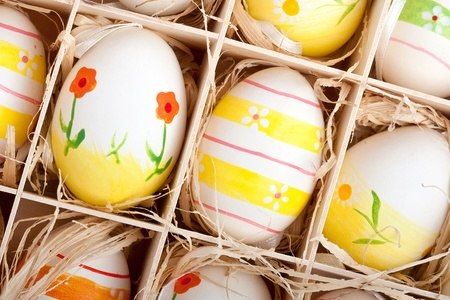 closeup of assorted colorful painted easter eggs in a wodden box