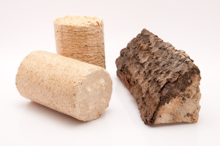 closeup of a piece of firewood and a wooden briquette isolated on white background