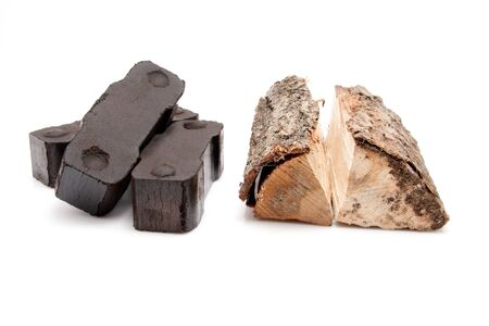 closeup of a pile of three coal briquettes and two pieces of firewood isolated on white background  Stock Photo