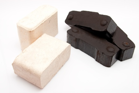 briquettes: closeup of a pile of three coal briquettes and two pieces of wooden fire briquettes isolated on white background