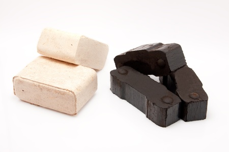 closeup of a pile of three coal briquettes and two pieces of wooden fire briquettes isolated on white background