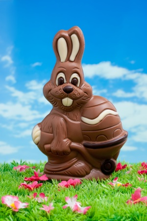 Easter bunny made ??of chocolate with easter egg on a green meadow with flowers in front of a blue sky with white clouds