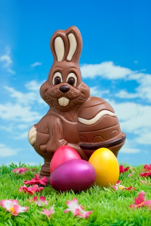 Easter bunny made of chocolate with colorful easter eggs on a green meadow with flowers in front of a blue sky with white clouds